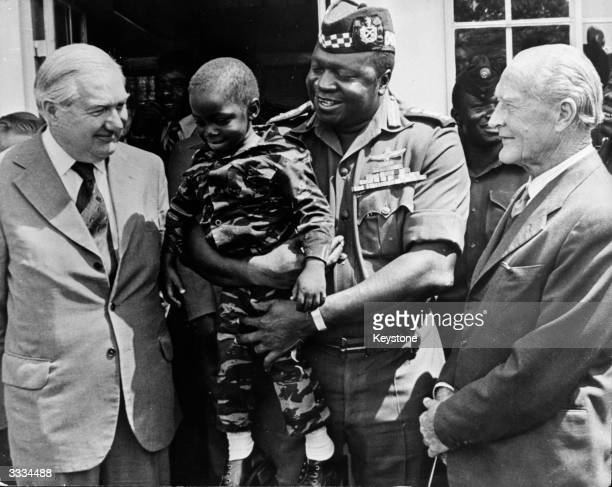 President Amin of Uganda with his young son, Mwanga dressed as a commando. Watching are James Callaghan and Denis Hills who had been released from...