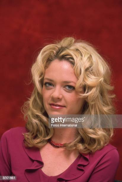Headshot studio portrait of American actor Lisa Robin Kelly wearing a fuchsia blouse with a ruffled neckline sitting in front of a red backdrop...