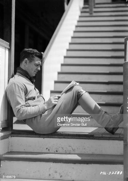 American leading man Clark Gable relaxing on a staircase.
