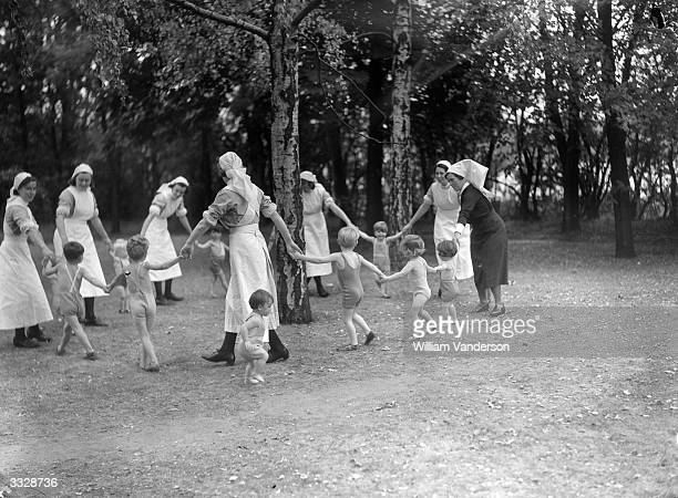 Nannies and toddlers playing in the garden at Coaxden Babies Home, Uxbridge, England.