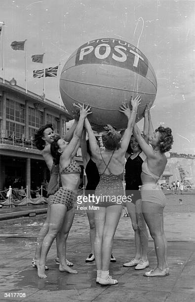 Bathing belles at Brighton hold aloft a large beach ball inscribed 'Picture Post' Original Publication Picture Post 171 Brighton pub 1939