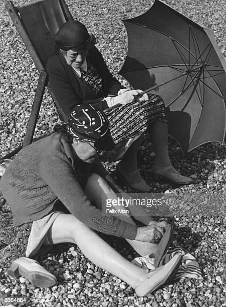 Women shading themselves on the beach in Brighton Original Publication Picture Post 171 Brighton pub 1939