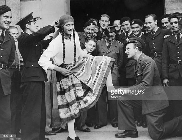 One of the Polish airmen undergoing intensive training at a British RAF base dons a feminine Polish national costume before performing in a male...