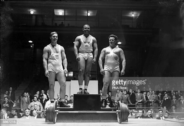 The three winners of the Super Heavyweight Weightlifting at the 1948 London Olympics take their places on the podium In first place is John Davis of...