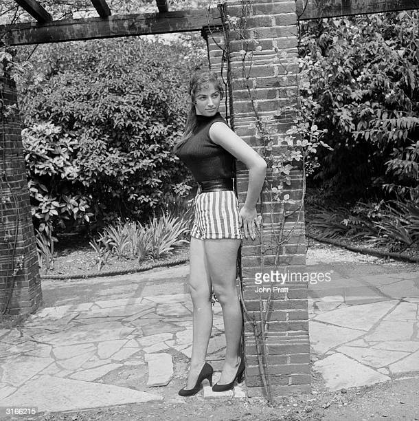 Seventeen year old British actress and author Jackie Collins posing in striped shorts and a snug fitting top