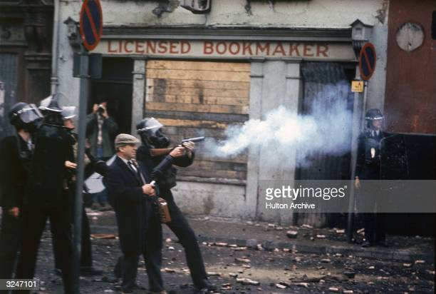 Police wearing gas masks fire cartridges of tear gas in front of a bookmakers during the Ulster riots in Londonderry Northern Ireland