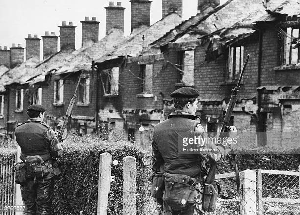 British soldiers stand on guard over houses that have been wrecked by bombs fired by the IRA in the central area of Belfast