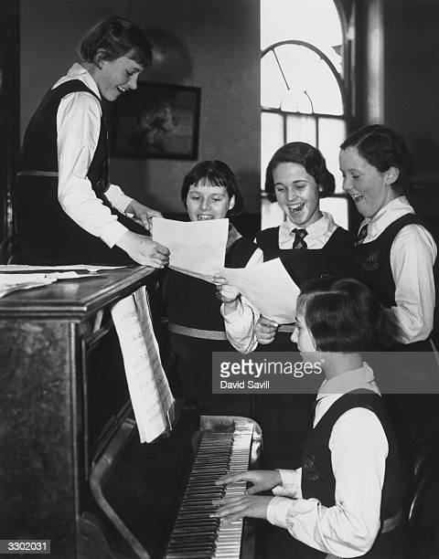Girls from the Licensed Victuallers School in Slough practising Christmas carols around the piano