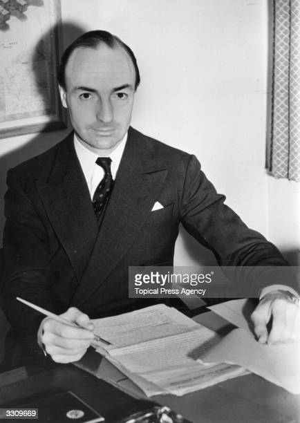 Parliamentary secretary to the Ministry of Civil Aviation John D Profumo OBE working at his desk at Ariel House