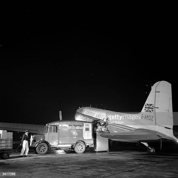 Loading mailbags onto the plane which will take overnight mail from Manchester's Ringway Airport to Ireland. Original Publication: Picture Post -...