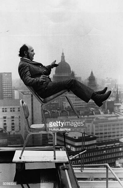 A man balances on two chairs on a roof top high above the City of London The dome of St Paul's Cathedral is in the background