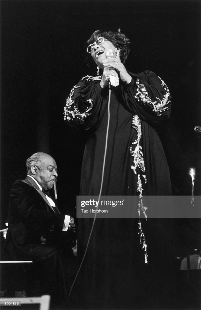 American jazz pianist, composer and bandleader Count Basie (1904-1984) performs with American jazz singer Ella Fitzgerald (1917-1996) during a concert at the San Antonio Arena, San Antonio, Texas. Basie wears a tuxedo. Fitzgerald wears a long dark gown with jeweled trim.