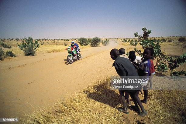 12th edition od the ParisDakar rallye A group of youth observes the pass of a motorbyke for the desert