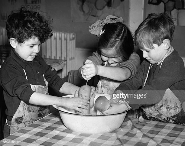 Three children giving a couple of dolls a bath at Brockley Road Infants' School, Lewisham.