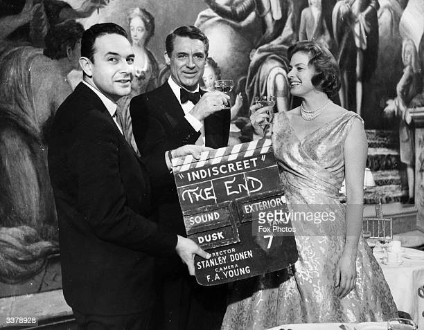 Director Stanley Donen holds up the final clapperboard as the stars Cary Grant and Ingrid Bergman celebrate the completion of their latest film...