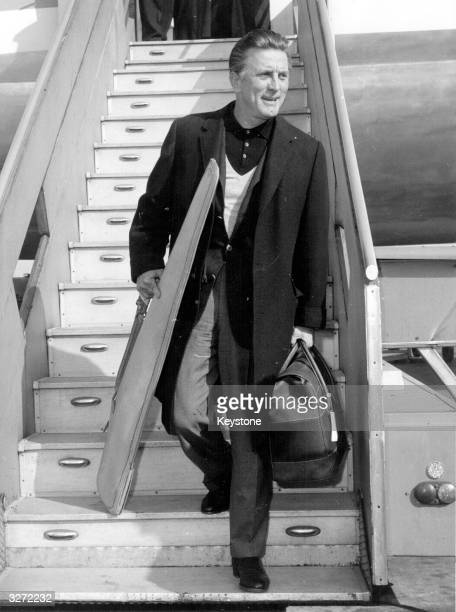 American actor Kirk Douglas arriving in Rome carrying a big gun for his Kenyan safari