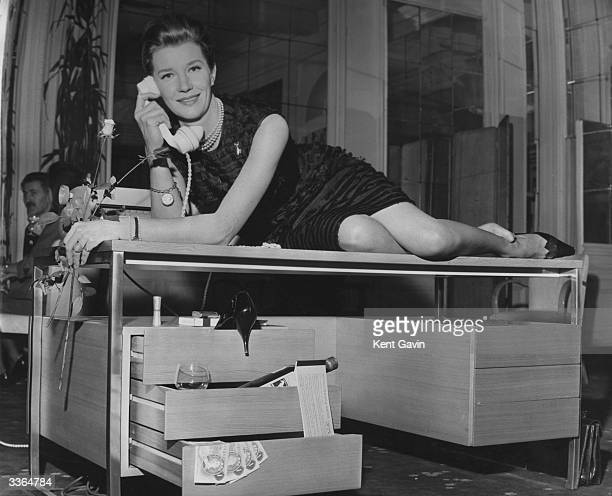 Actress Lois Maxwell, who plays the part of M's secretary Miss Moneypenny in the James Bond films, reclining on a newly-designed desk by Intra Design...