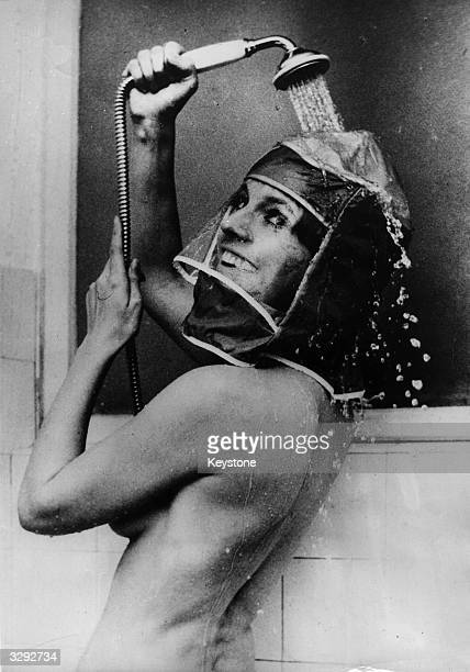 Munich actress Inge Marschall demonstrates use of the new showerhood invented in Germany to protect hair and makeup in the shower