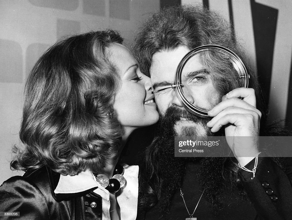 Pop singer and songwriter Roy Wood of the group Wizzard peers at the award he has just received for being the Top Musician in the Disc Music Poll, whilst he is kissed by American model Rose Marie, who presented it to him.
