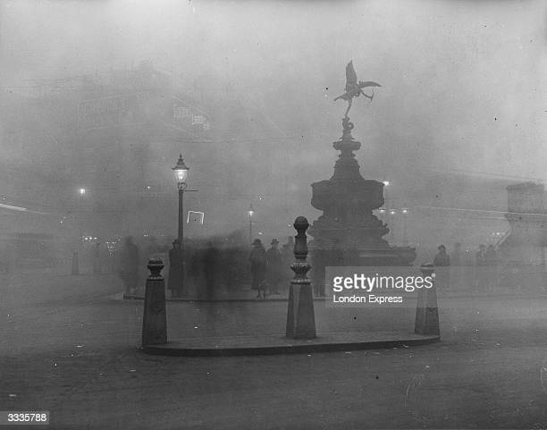 The famous statue of Eros at Piccadilly Circus is barely visible in the London fog