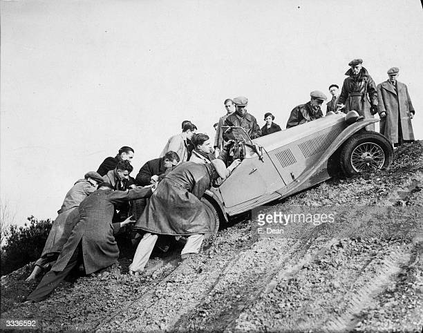 Group of men helping a competitor get up a steep hill Great West Motor Club's Haward Tanker Trial at Camberley Heath Surrey England