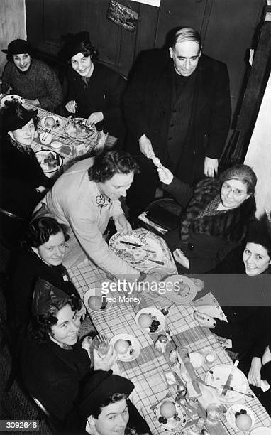 Rev J R Sankey of St Andrews in the Wardrobe London helps to pull a cracker at a New Year lunch in a club set up for City of London women workers The...