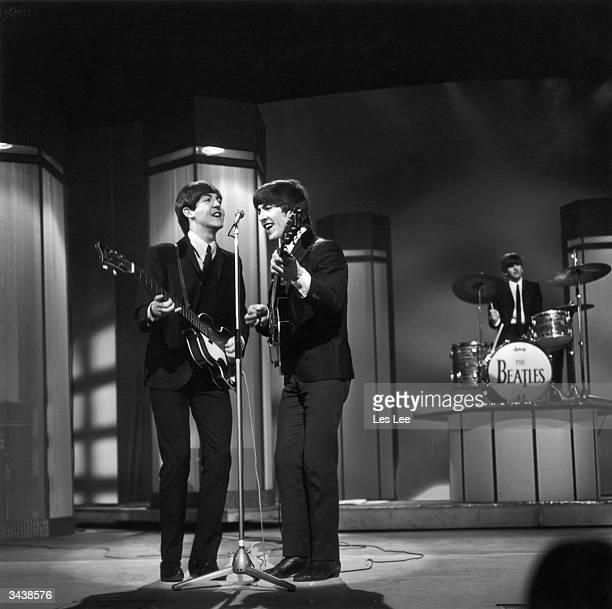 Paul McCartney and George Harrison performing at the London Palladium Drummer Ringo Starr is in the background