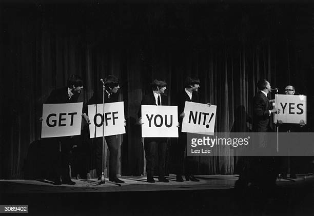 The Beatles on stage at the London Palladium hold placards saying,'Get Off You Nit'.