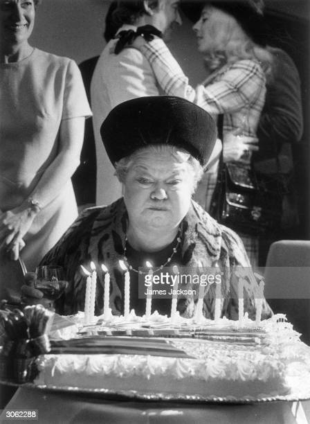 Violet Carson who plays Ena Sharples in the TV soap 'Coronation Street' blows out the candles at the show's 10th anniversary celebrations held at the...