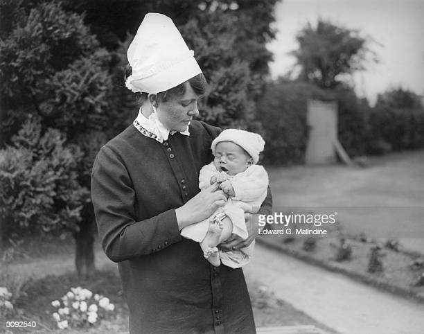 A nurse holding a two month old baby that was found partially buried in a rabbit hole at a wood in Haremare Hill Sussex England