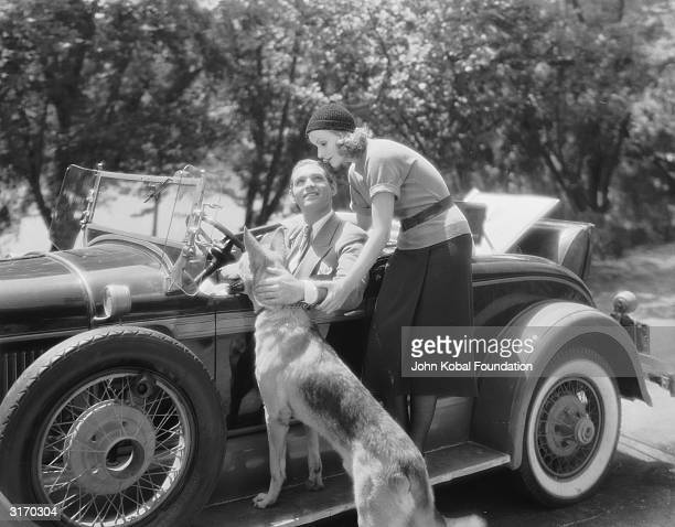 American actor Clark Gable sits in his car chatting to Swedish born actress Greta Garbo while stroking a german shepherd dog in a scene from the film...
