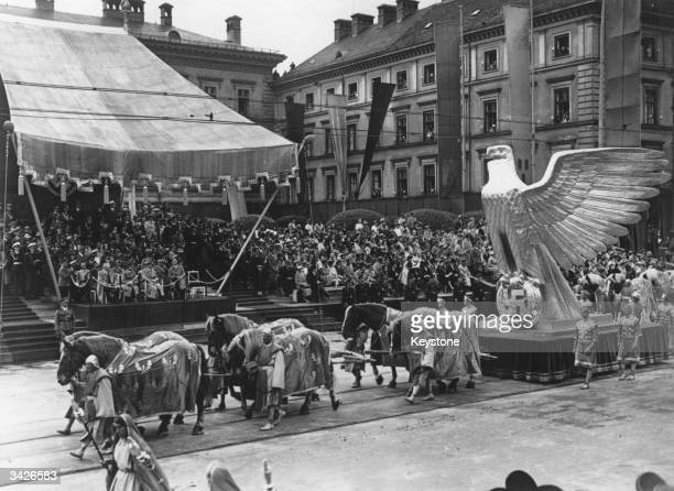 A large model of the German eagle carrying a laurel wreath and swastika passing Hitler after he had opened the Nazi art exhibition in Munich