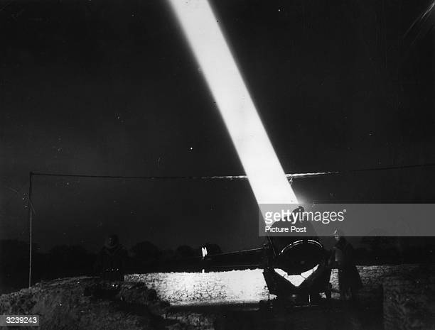 A projector controller directs a searchlight beam into the night sky Original Publication Picture Post PP 303 Searchlights Pub 1940