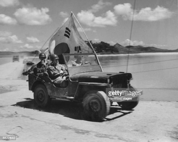 A South Korean jeep carrying a flag to identify themselves to American airmen falling back to cover Taejon in the South Original Publication Picture...