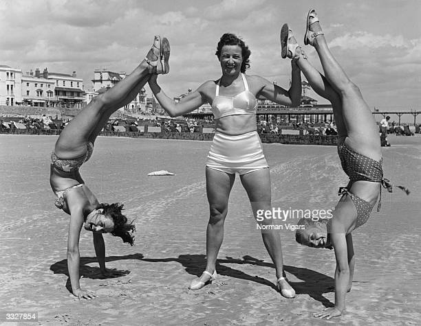 Holiday-makers Doris, Betty and Rose strike an unusual pose on the beach at Bognor Regis.
