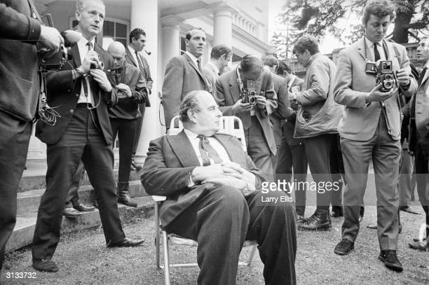 British actor Robert Morley relaxing amidst a crowd of photographers during a visit by the England football team to Pinewood Studios Russian actor...