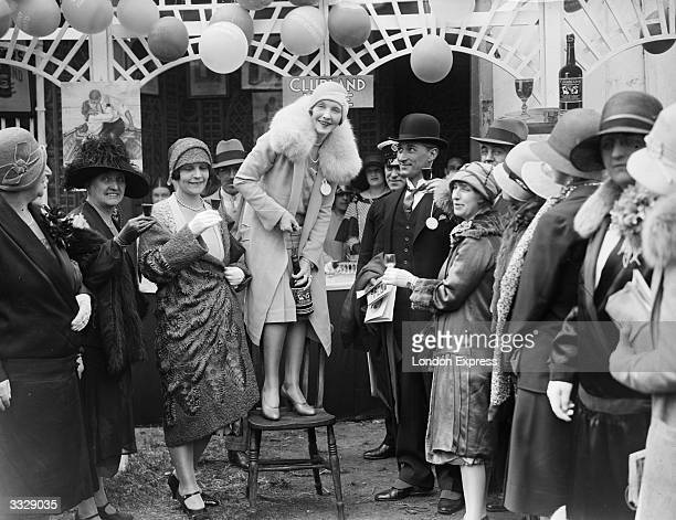 A woman drawing a cork at a theatrical garden party surrounded by guests