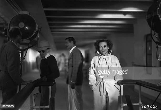 American actor Joan Crawford smiles while posing in front of Clark Gable and director Clarence Brown on the set of Brown's film 'Chained' Crawford...