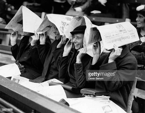 A group of spectators watching the Wightman Cup tennis tournament at Wimbledon London use their newspapers to shelter from the rain