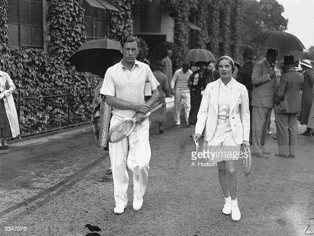British tennis player Kay Stammers walks onto the court with coach Dan Maskell for a knockup before her match against Helen Jacobs of the USA in the...