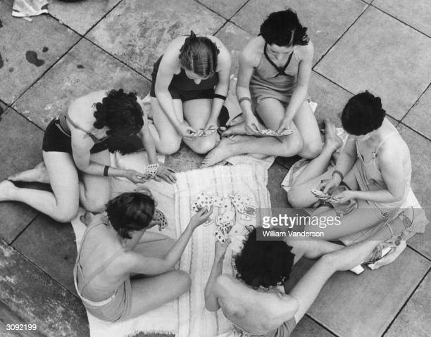 Group of bathers enjoy a quiet game of cards whilst basking in the sunshine at the Hornsey open-air swimming baths.