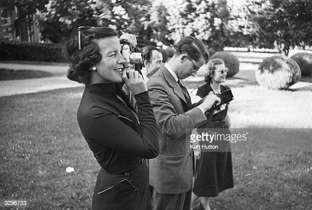Princess Marie Lilian de Rethy wife of King Leopold III of Belgium takes a photograph in the garden of their villa in Pregny Geneva where they are in...