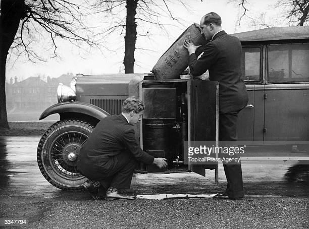An ordinary Humber Snipe Tourer which has been converted to run on charcoal The car is being filled with fuel by its inventor Mr Goldman left and his...