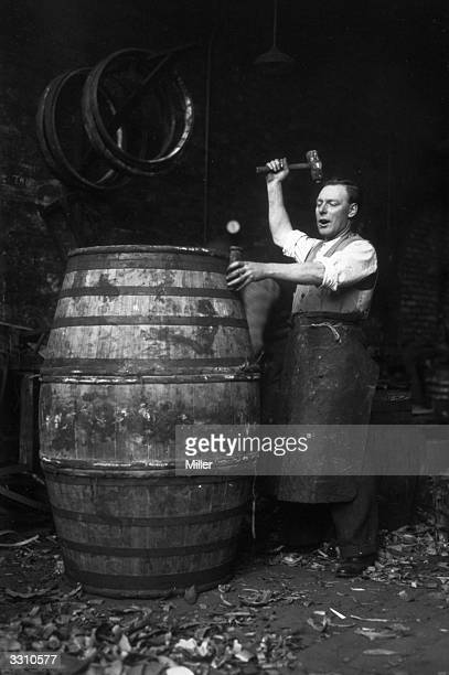 John Harrison the Singing Cooper strikes some high notes as he strikes a barrel in a coopers yard in Bermondsey London
