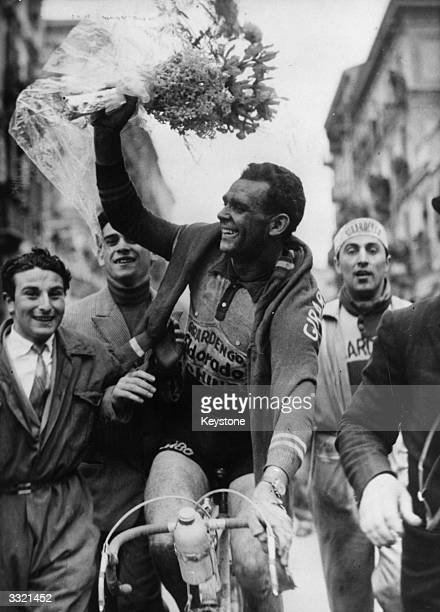 Belgian cyclist Rik Van Steenbergen waves the traditional bouquet of flowers after winning the MilanSan Remo cycle race on the Italian Riviera