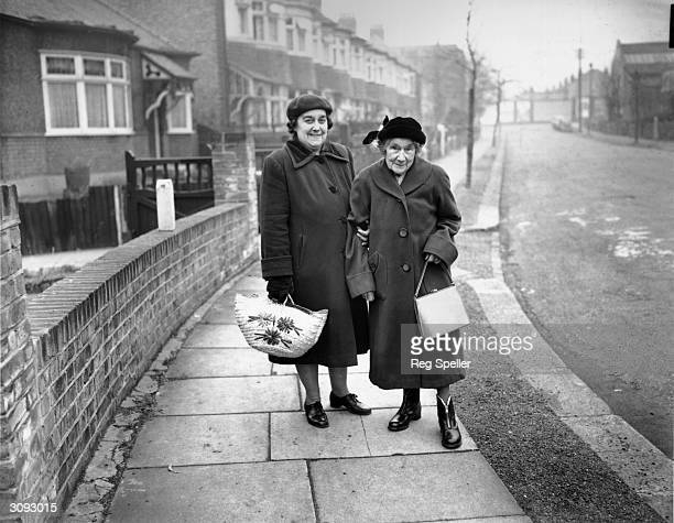 101yearold Mrs Agnes Emily Gamlen of Palmers Green London on her way to the shops with her neighbour Mrs Rosa Arnott