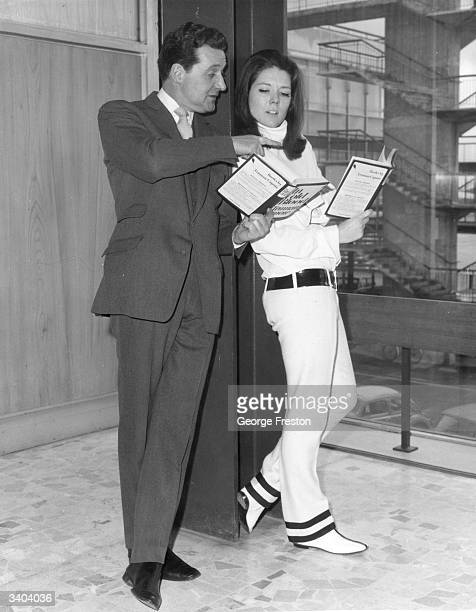 Actors Patrick Macnee and Diana Rigg, reading Truman Capote's 'In Cold Blood' as they wait at London Airport to travel across the United States to...