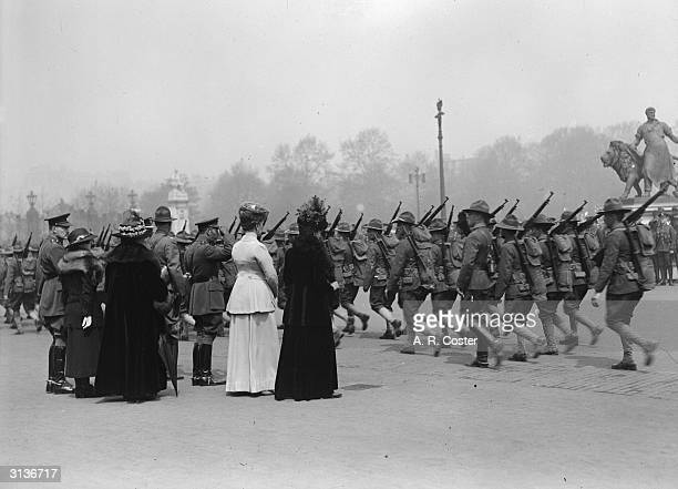 King George V takes the salute as American soldiers parade past the Royal party outside Buckingham Palace