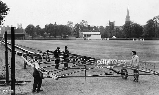 Cyril Coote and some of his men finishing of a novel wicket cover, made from old iron bedsteads and then covered with canvas, for Fenners Ground,...