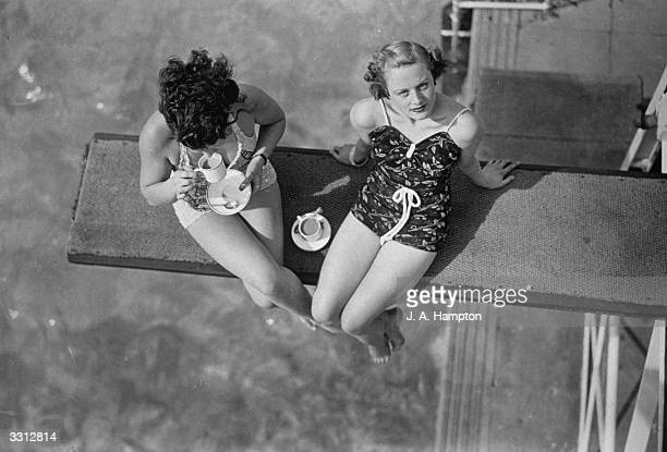 Two women having tea on the diving board at Finchley swimming pool London